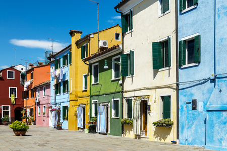 Colorful buildings in Burano island sunny street, Venise, Italy photo