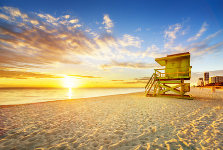 panoramic beach: Miami South Beach sunrise with lifeguard tower and coastline with colorful cloud and blue sky.