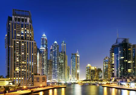 skyline of Dubai Marina at night with boats, United Arab Emirates, Middle East photo
