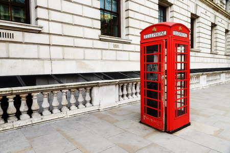 ly: Red telephone near Big Ben in London England the UK. One of the symbols of London city.