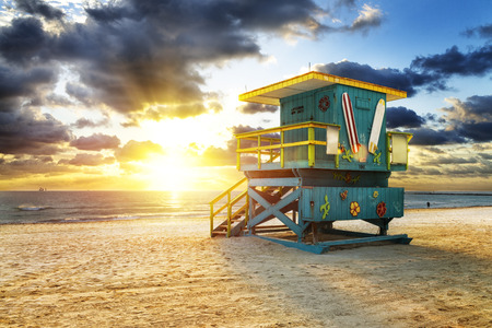 south beach: Miami South Beach sunrise with lifeguard tower and coastline with colorful cloud and blue sky.