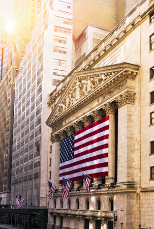 building of the wall: Famous Wall street and the building in New York, New York Stock Exchange with patriot flag