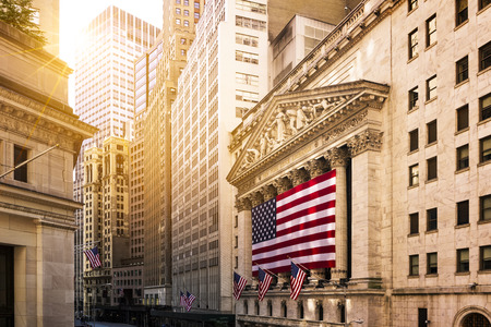 turmoil: Famous Wall street and the building in New York, New York Stock Exchange with patriot flag