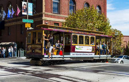 frisco: SAN FRANCISCO - OCT 06: Passengers enjoy a ride in a cable car on Oct 06, 2012 in front of famous Transamerica building in San Francisco. It is the oldest mechanical public transport in San Francisco which is in service since 1873. Editorial