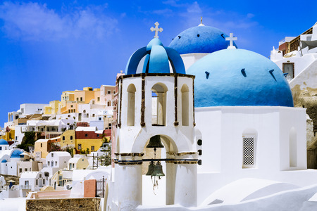 sea of houses: Oia town on Santorini island, Greece. Traditional and famous houses and churches with blue domes over the Caldera, Aegean sea Stock Photo
