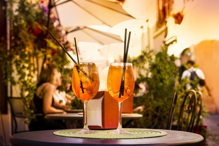 spritz: Aperol Spritz Cocktail. Alcoholic beverage based on table with ice cubes and oranges.
