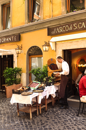 italy street: Rome, Italy - May 27, 2016: Unidentified people eating traditional italian food in outdoor restaurant in Trastevere district in Rome, Italy.