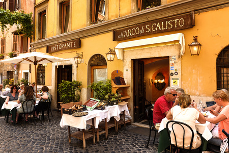 restaurante italiano: Rome, Italy - May 27, 2016: Unidentified people eating traditional italian food in outdoor restaurant in Trastevere district in Rome, Italy.
