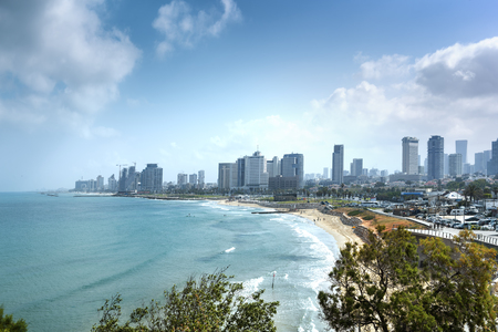 est: Tel Aviv skyline by day with beach, sea and waves