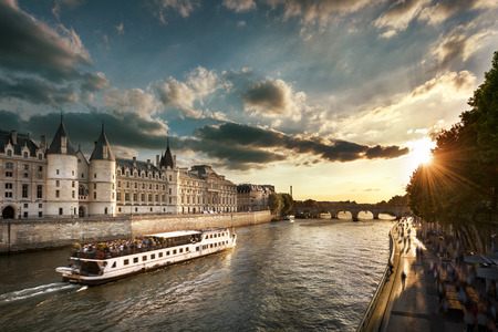cite: Consiergerie, Pont Neuf and Seine river with tour boat at sunny summer sunset, Paris, France