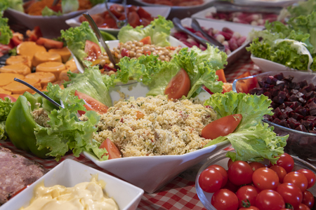 Tasted and various food and salads, tomatoes, taboule, sals in a restaurant table