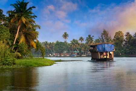 A traditional house boat is anchored on the shores of a fishing lake in Kerala's Backwaters, Kerala, India 免版税图像