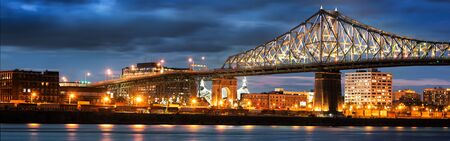 Jacques Cartier Bridge Illumination in Montreal, reflection in water. Montreal? ? ? s 375th anniversary. bright colorful interactive Jacques Cartier Bridge. Bridge panoramic colorful silhouette by night Фото со стока
