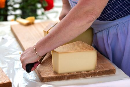 woman is saling swiss gruyere cheese in the market of Charmey, Fribourg, switzerland Stock Photo