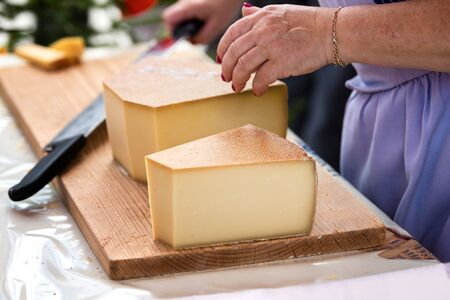 woman is saling swiss gruyere cheese in the market of Charmey, Fribourg, switzerland