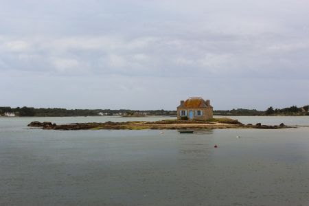 photograph of a house by the sea surrounded by sea photo