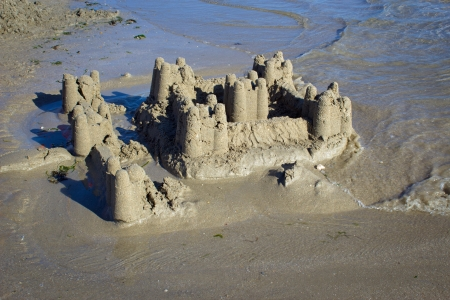 destroying: photograph of a sand castle collapsing by the tide on the coast of Brittany