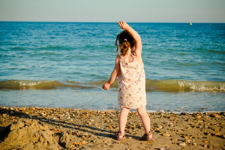 photograph of a girl throwing rocks into the sea Stock Photo