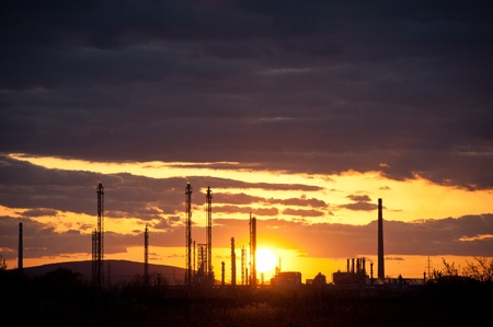 silhouette of oil refinery at sunset photo