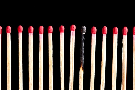 a row of matches with one burned, isolated on black background