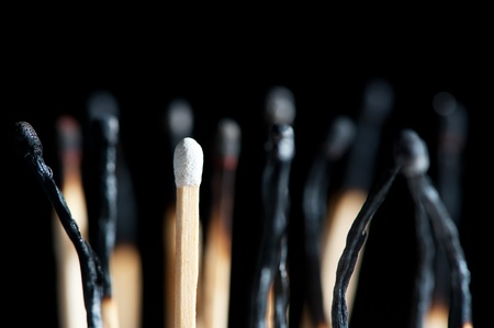 burned matches, only one in front has not been used, black background Stock Photo