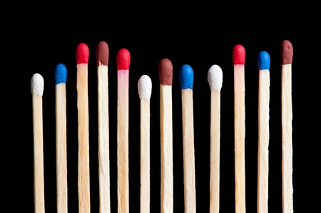 match with white, red, blue and brown head in line, black background Stock Photo