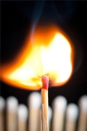 burning match in front of others in background
