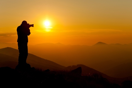 silhouette of photographer taking picture of landscape during sunset