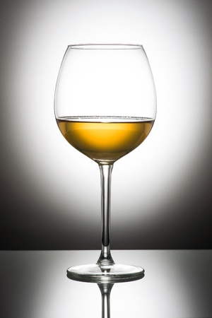 Glass of white wine with reflection on white background