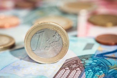 One euro coin, other euro coins and notes in background