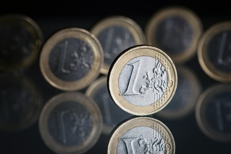 One euro coins on black background with background photo