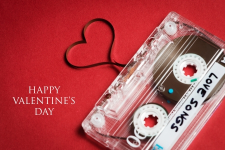 song: Valentines day card - audio cassette with magnetic tape in shape of heart on red background