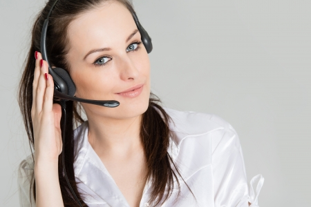 Portrait of phone operator with headset, grey background Stock Photo