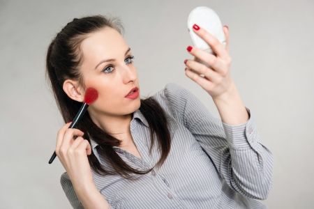 Portrait of a young woman applying make up, grey background photo
