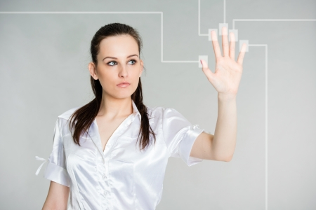 young attractive brunette looking at her hand during scan of her fingers on a touch screen interface, gray background