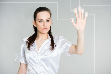 young attractive brunette looking at you during scan of her fingers on a touch screen interface, gray background photo