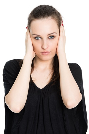 Hear no evil - attractive young brunette covering her ears with hands, isolated on white background