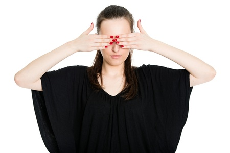 See no evil - attractive young brunette covering eyes with her hands, isolated on white background