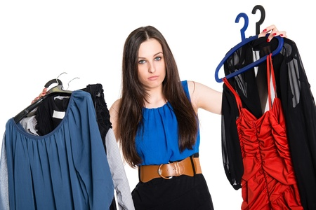 Doubtful brunette choosing which dress to wear, isolated on white background Stock Photo