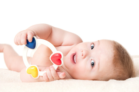 Cute six months old baby boy playing with a rattle, isolated on white background