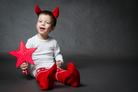 cute little boy with devil horns and red star, gray background