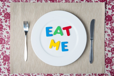Concept  healthy food and diet - word EAT ME on a white plate photo