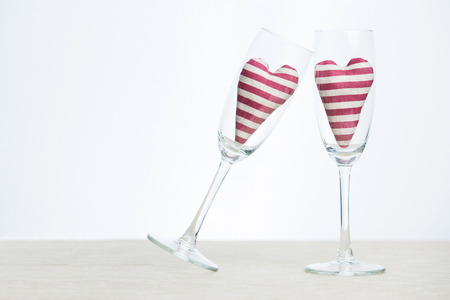 Valentine concept - two stripped hearts in champagne glasses photo