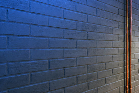 detail of gray brick wall with blue light Stock Photo
