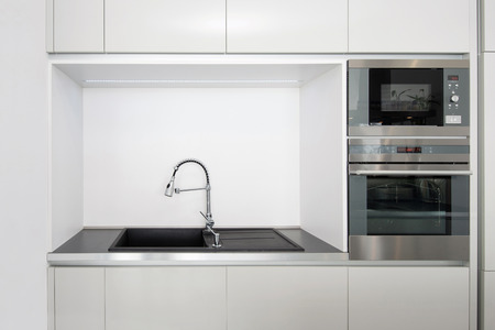 Detail of kitchen built-in appliances and faucet with sink