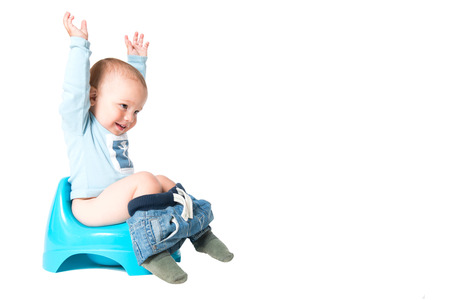 Happy one year old boy having fun on the chamber pot, isolated over white background