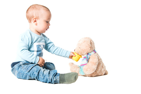 One year old boy with feeding his teddy bear, isolated over white background