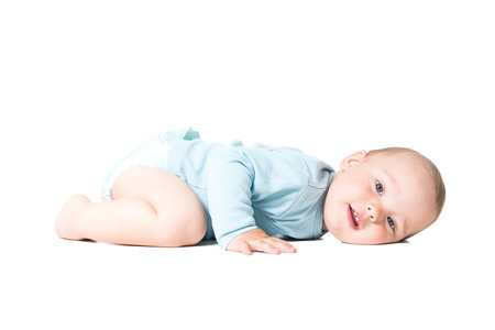 Adorable year old kid lying on the floor, isolated over white background photo