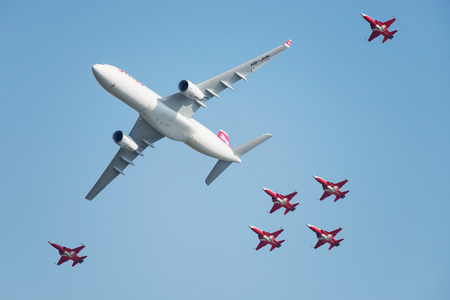 aerobatic: PAYERNE, SWITZERLAND - SEPTEMBER 6: Flight of Airbus A-330 of Swiss Airlines followed by Patrouille Suisse aerobatic team in close formation on AIR14 airshow in Payerne, Switzerland on September 6, 2014