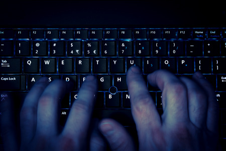 data theft: hands typing on keyboard in blue light with motion blur